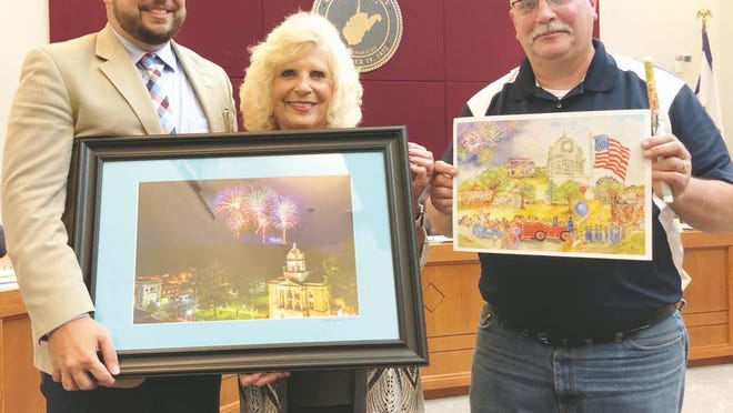 Buchannon mayor Robbie Skinner (left) presents Mayor Carolyn Rader with a Ripley Fourth of July fireworks photo. Councilman John McGinley (right) gifts Skinner with a print by former mayor and artist Willa McGinley, along with a commemorate Ripley pen.