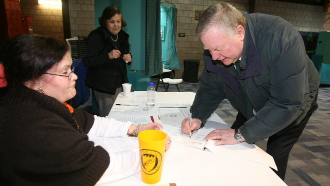 Acting Tuckahoe Justice Michael O'Toole signs the election register as he prepares to vote in the village's election at Tuckahoe Community Center March 18, 2014. Looking on are election inspectors Virginia Marciano and Adelaide DiGiorgi.
