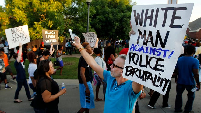 Todd Whitley, center, of Hope for Peace and Justice showed his support June 8, 2015, for protesters who marched outside the Craig Ranch subdivision pool where McKinney police Cpl. Eric Casebolt was seen on video pinning a 15-year-old black girl to the ground and pointing his gun at other teens.