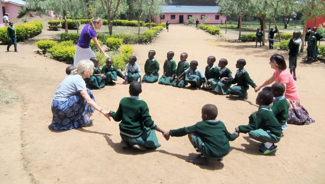 Brighton resident Priscilla Watts, standing, and two missionaries play a game with Kondoa Integrity School students.