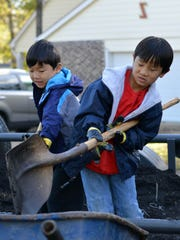 Alexander and Edward Moody shovel mulch to help landscape Donna Reiss's yard as part of a service project to raise money for the adoption of their baby sister from Poland.