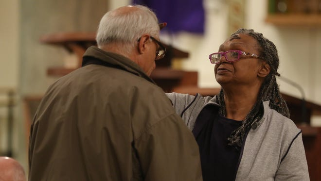 Carletta Manywether of Rochester and church member gives ashes to Frank Paparone of Greece.