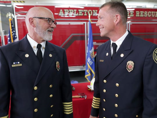 Retired Appleton Fire Chief Len Vander Wyst, left, talks to  new Fire Chief Jeremy Hansen   following a swearing-in ceremony Monday in Appleton.