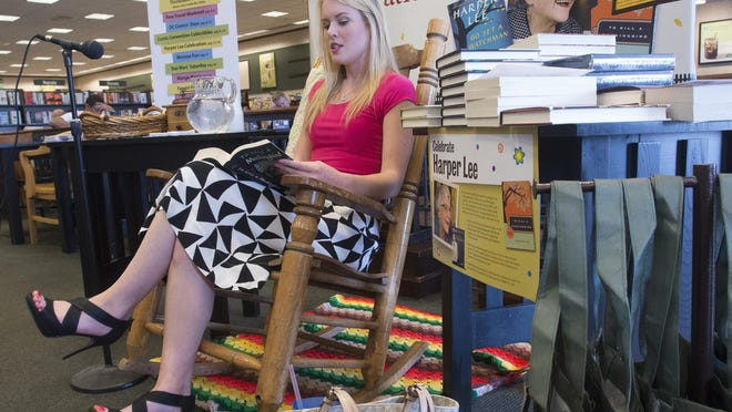"""Carly Borden, co-host of the Daily Brew on Blab TV, reads a passage from the book """"To Kill a Mockingbird"""" by Harper Lee at Barnes and Noble on Airport Blvd. Monday afternoon. Local celebrities began reading the literary classic one day before the release of Lee's new book, """"Go Set A Watchman."""""""