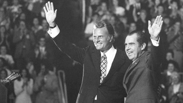 FILE - In this Oct. 16, 1971 file photo, Evangelist Billy Graham and President Nixon wave to a crowd of 12,500 at ceremonies honoring Graham at Charlotte, N.C.   Graham, who transformed American religious life through his preaching and activism, becoming a counselor to presidents and the most widely heard Christian evangelist in history, has died. Spokesman Mark DeMoss says Graham, who long suffered from cancer, pneumonia and other ailments, died at his home in North Carolina on Wednesday, Feb. 21, 2018. He was 99. (AP Photo, File)