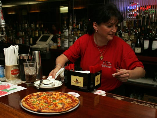 Ellen Gatta of Wall brings a sausage and pepper pizza to the bar at Vic's in Bradley Beach.