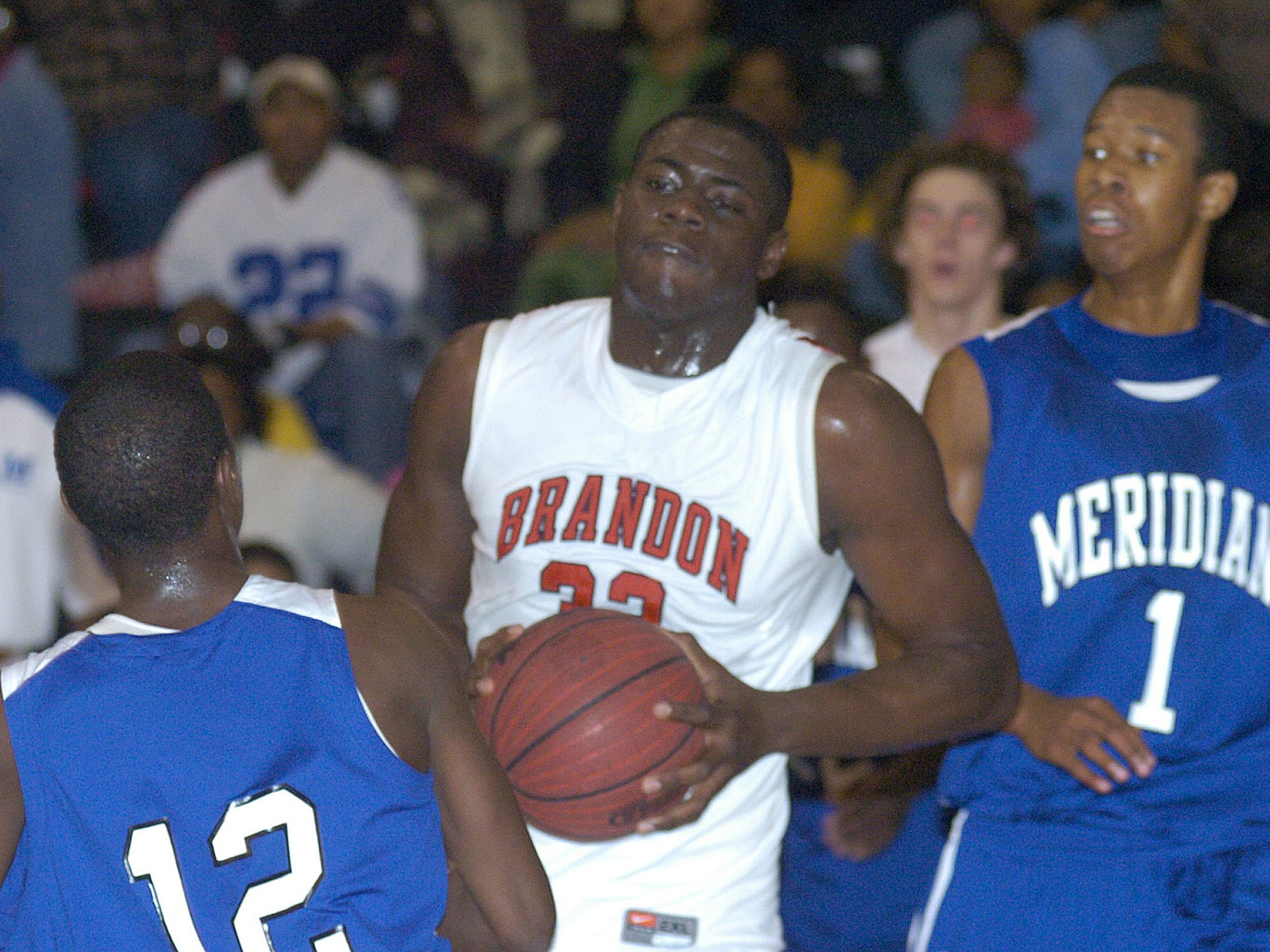 Brandon's Tyler Adams (center) drives to the basket against Marcus Hurn (left) and Rodney Hood of Meridian.