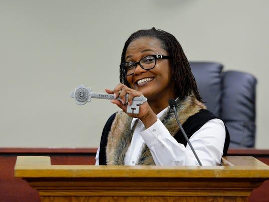 "Mayor C. Kim Bracey holds up the ""key to the city"""