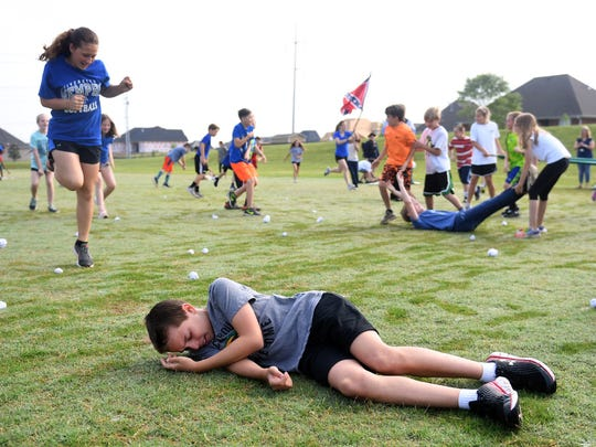 """Medina Middle School fifth grader Austin Shipley lays """"injured on the ground during as other fifth graders re-enact the Civil War, Thursday, May 17, 2018."""