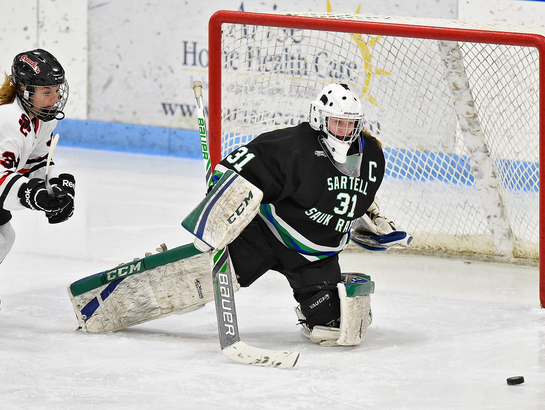 The puck skips past Sartell/Sauk Rapids goaltender Clare Minnerath and Megan Millroy of the Icebreakers during the first period of Thursday's game at the MAC in St. Cloud.