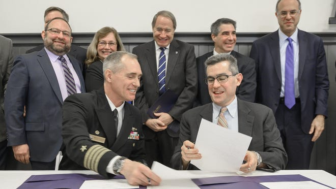 Capt. Michael R. Coughlin, commanding officer at the Naval Undersea Warfare Center and Christian Cowan, director of Polaris MEP, complete the ceremonial signing of the Partnership Intermediary Agreement for the 401 Tech Bridge Advanced Materials Center, in December 2019 at Innovate Newport.