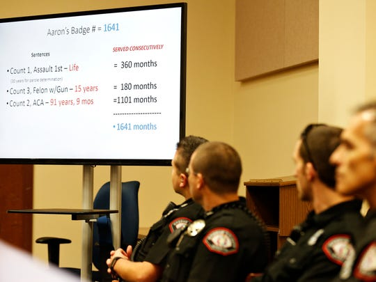 Police officers look at a proposed sentence laid out by prosecuting attorney Dan Patterson during the sentencing hearing of Joshua Hagood, who was found guilty in the shooting of police officer Aaron Pearson last year, at the Greene County Courthouse in Springfield, Mo. on Oct. 19, 2016.