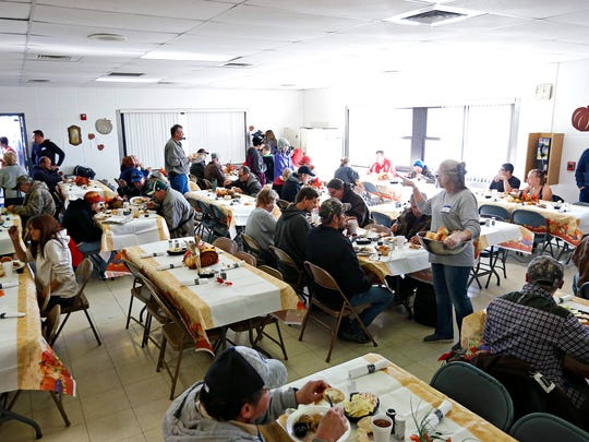 Volunteers walk between tables during the Salvation Army's annual Community Thanksgiving Lunch served at the Salvation Army Harbor House in Springfield, Mo. on Nov. 24, 2016.