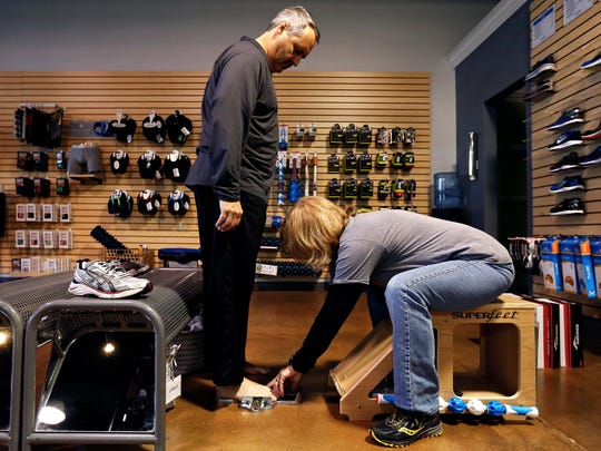 Todd Ruff has his feet measured by sales associate Yawnna Hamisak during Black Friday shopping at Feet Fleet Sports in Springfield, Mo. on Nov. 25, 2016.