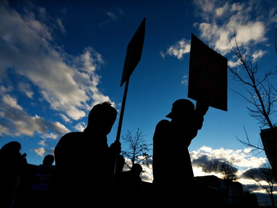 Attendees carry signs while marching during a rally