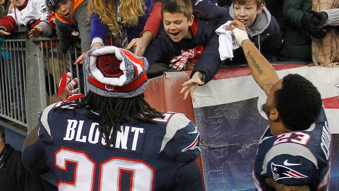 Dec 14, 2014; Foxborough, MA, USA; New England Patriots running back LeGarrette Blount (29) and safety Patrick Chung (23) hand their gloves to fans after a win over the Miami Dolphins at Gillette Stadium. New England defeated Miami 41-13. Mandatory Credit: Stew Milne-USA TODAY Sports