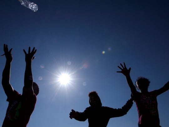 (from left) Alexander de la Rosa, 9, Riqueilin de la Rosa, 15, and Amber de la Rosa, 13, play catch with a bottle of water at Garret Mountain Reservation during an unusually warm day on Wednesday, February 21, 2018.