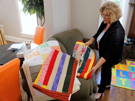 Debbie Joslin, the executive director of the Children's Hope Foundation, holds a quilt donated to the nonprofit organization at the foundation's office on Wednesday.