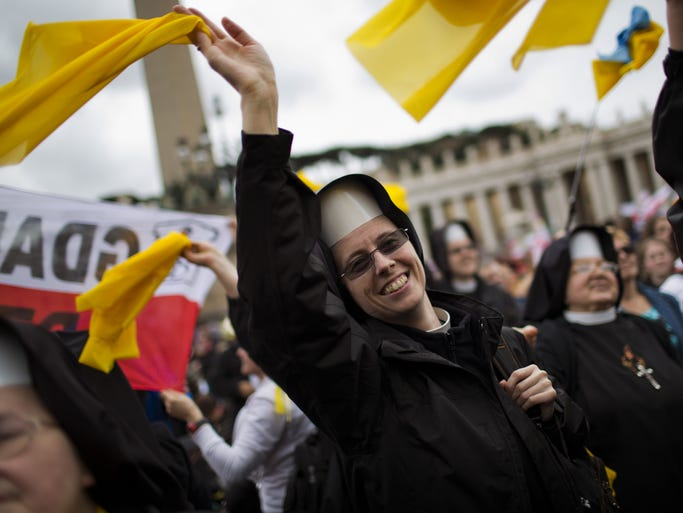 Nuns wave as Pope Francis is driven through the crowd after presiding over a solemn ceremony in St. Peter's Square at the Vatican, Sunday, April 27, 2014. Pope Francis has declared his two predecessors John XXIII and John Paul II saints in an unprecedented canonization ceremony made even more historic by the presence of retired Pope Benedict XVI.