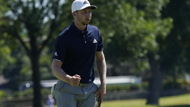 Daniel Berger pumps his fist after a birdie putt on the 18th hole during Sunday's final round of the Charles Schwab Challenge at the Colonial Country Club in Fort Worth, Texas. Berger, at right, holds the championship trophy after defeating Collin Morikawa on the first playoff hole. DAVID J. PHILLIP PHOTOS/AP