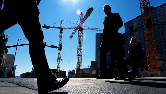 Cranes loom behind pedestrians in downtown Nashville at the construction site of a 45-story skyscraper.