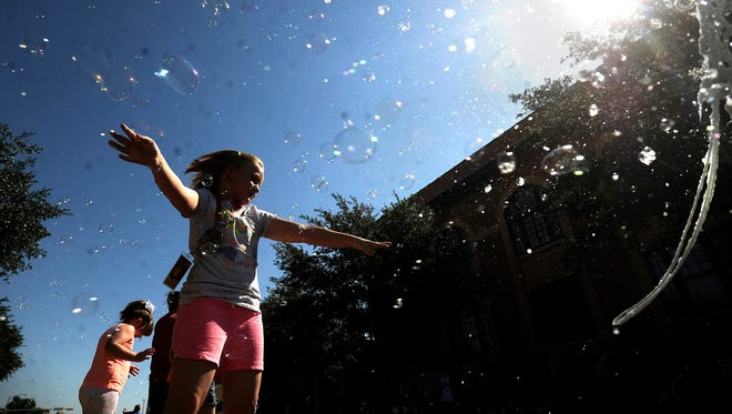 Mollie Sears, 8, from Albany, plays in the bubbles on Cedar Street during the Children's Art & Literacy Festival on Saturday, June 10, 2017, in downtown Abilene.
