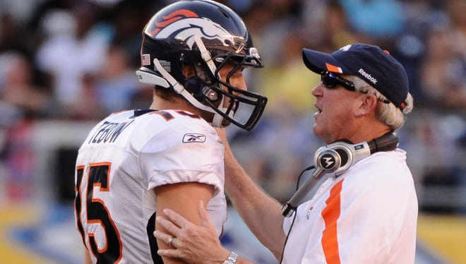 Former Denver Broncos quarterback Tim Tebow (15) talks to head coach John Fox during the second half of the Broncos' win over the Chargers at Qualcomm Stadium.