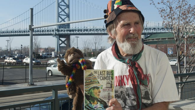 """Rocky Wilson shows his book, """"Last Bus to Camden,"""" and his friend, Bongo."""