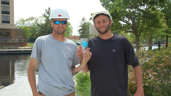 Cement workers take a break to pose with a commemorative Shore Craft Beer Fest glass.