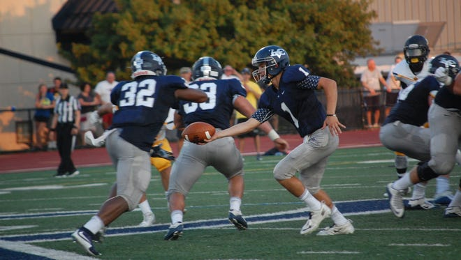 Lebanon Valley quarterback Tim Pirrone hands off to running back Jon Jones (32) in a game against Wilkes on Saturday evening.