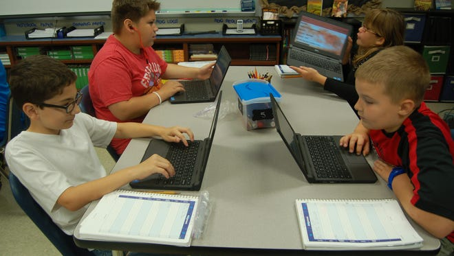 Four students at Hackler Intermediate School work on Google Classroom assignments Thursday. Google Classroom allows teachers to send assignments, lessons and projects to students.