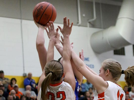 Williamsburg's Peyton Fisher tries to shoot the ball over Versailles players Ellen Peters and Catlin McEldowney.