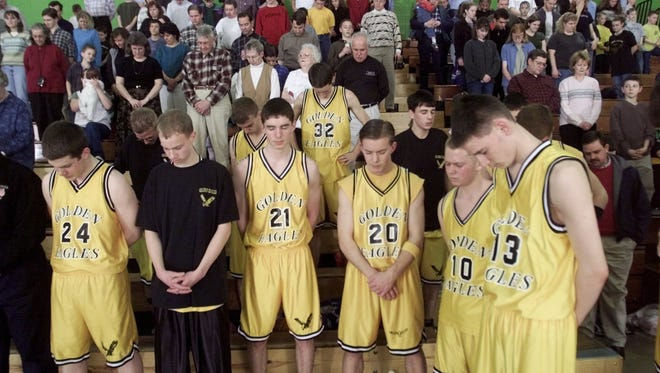 Members of the Golden Eagles, a team of home-schooled students,  pray before the start of a game against the Lions Club at Creston Jr. High in 2001.