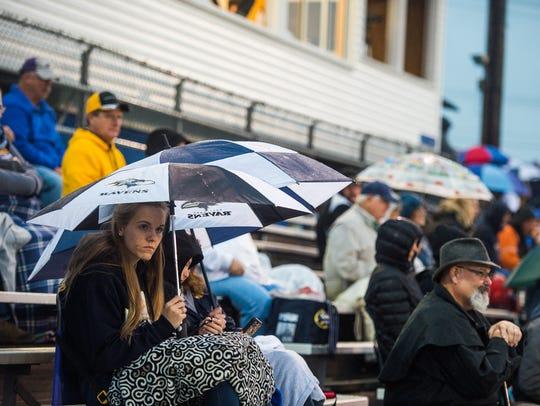 Football fans huddle under umbrellas Friday night Sept.