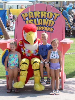 Lyncoln Groda, 4, from left, Wesley Jeffers, 8, and Lyla Wibbing, 5, have their picture taken with Petey the Parrot, Monday, September 7, during a visit to Parrot Island Waterpark with Monica and Bryan Groda on the last day of the waterpark's 2020 season.