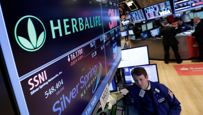 FILE - In this Jan. 23, 2014 file photo, Specialist Peter Elkins foreground, works at the post that handles Herbalife, on the floor of the New York Stock Exchange.  Herbalife's stock is surging 12 percent in premarket trading Friday, May 6, 2016 after the seller of supplements and weight-loss products disclosed that it's in advanced talks to potentially settle a federal investigation into claims that it's a pyramid scheme. (AP Photo/Richard Drew)