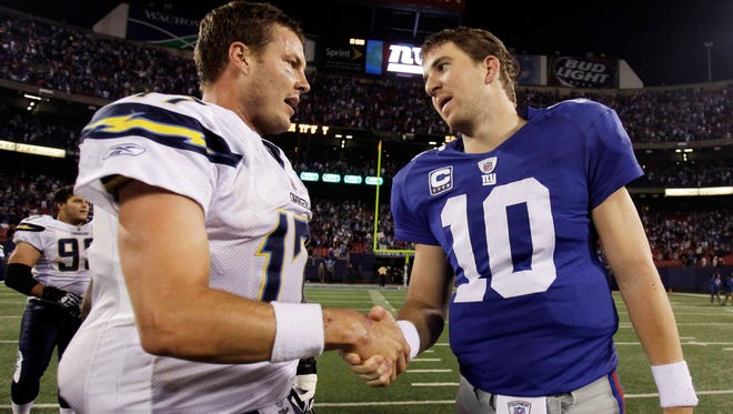 San Diego Chargers quarterback Philip Rivers, left, shakes hands with New York Giants quarterback Eli Manning after an NFL football game. Rivers takes over the quarterback consecutive starts streak now what Manning is being benched.