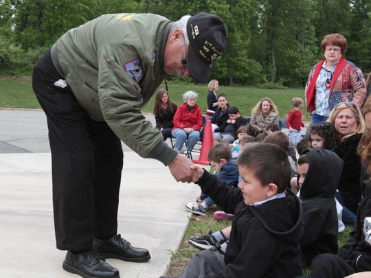 Vietnam veteran Woody Burgener shakes hands with Andrew Gauker, 5, at the start of the flag raising ceremony in observance of Memorial Day at Benedict A. Cucinella Elementary School in Long Valley in Washington Township.