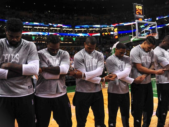 Members of the Boston Celtics pay tribute to the national
