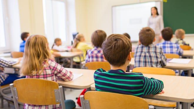 Students listen to a teacher in classroom