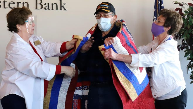 Members of the River Valley Stars Quilts of Valor, Sue Anderson, left, and Donna Hardin present Army veteran Jim Simon, with a personalized quilt, Friday, Oct. 30, during a ceremony at Booneville's Meeting Place, to recognize Simon, Jerry Wagoner and Amos Stropes, for their military service.