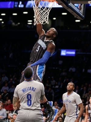 Orlando Magic guard Victor Oladipo (5) dunks over Brooklyn Nets guard Deron Williams (8) in the first half of an NBA basketball game, Wednesday, April 15, 2015, in New York. Brooklyn Nets forward Joe Johnson (7) watches, lower right. (AP Photo/Kathy Willens)