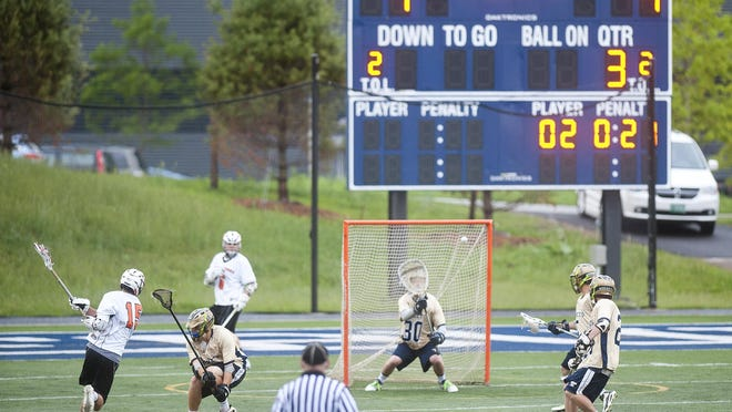 Middlebury's Connor Quinn, left, rips a shot at the Essex goal during the second half of Tuesday's Division I boys lacrosse semifinal at Middlebury College.