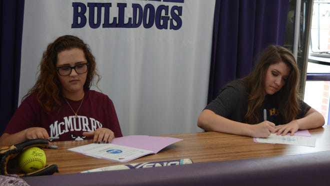 Wylie's Hailey Russell (left) and Gabby Zullo sign papers during their commitment ceremony Tuesday outside the Wylie High School gym. Russell will play softball at McMurry, while Zullo will play basketball at Hardin-Simmons.
