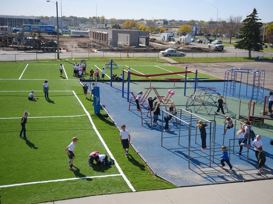 St Michael's School students play on the playground and turf field Wednesday, Oct. 18, in Sioux Falls. A volleyball court, soccer and football field are outlined on the playground turf.