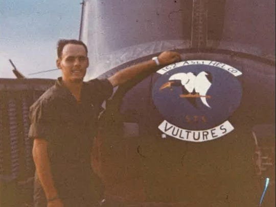 A young Floyd Stringer stands in front of a helicopter.