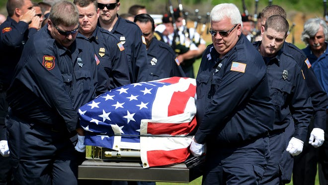 Madison County firemen carry the American flag-draped casket of Madison County Firefighter Chris Blankenship on Thursday at Highland Memorial Gardens.