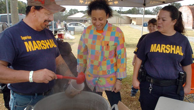 Deputy Marshal Frank Angelle prepares a sample bowl of gumbo for gumbo judge Maureen Little at Saturday's gumbo cook-off to benefit police officers and first responders. The event was held at the Yambilee Building.