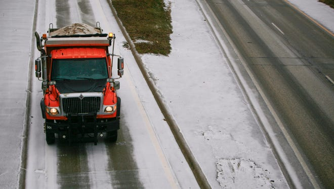 A truck loaded with sand merges onto 1-496 Monday, as Lansing prepares for icy weather.