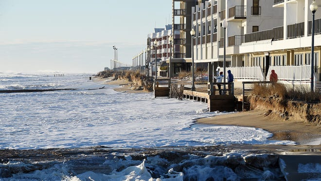 Crews work to clean up Sunday morning in Rehoboth Beach following coastal flooding. The storm caused severe coastal erosion and damage to the boardwalk.